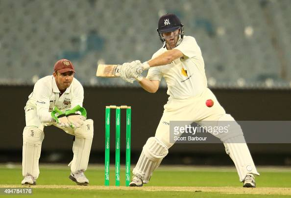 Travis Dean of Victoria bats as wicketkeeper Chris Hartley of Queensland looks on during day two of the Sheffield Shield match between Victoria and...