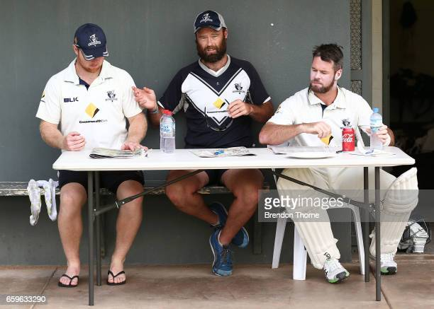 Travis Dean Rob Quiney and Dan Christian of the Bushrangers sit at a table on the sidelines during the Sheffield Shield final between Victoria and...