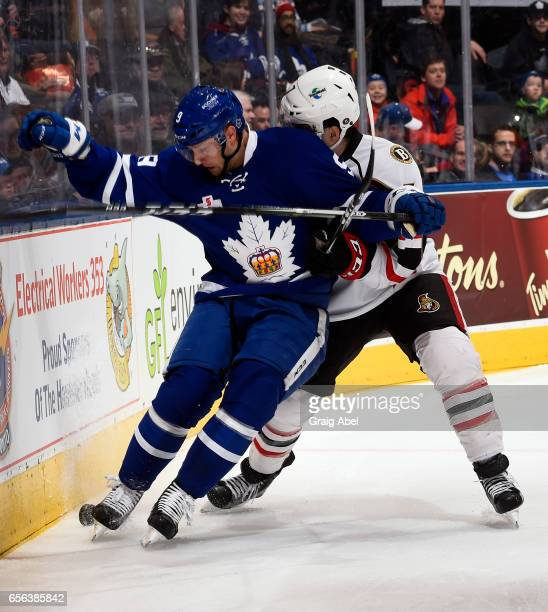 Travis Dermott of the Toronto Marlies battles for the puck with Chris Carlisle of the Binghamton Senators on March 18 2017 at Air Canada Centre in...