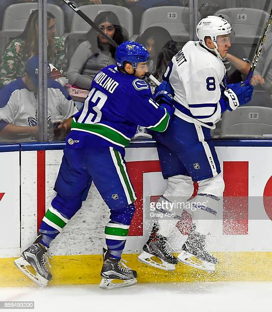 Travis Dermott of the Toronto Marlies puts a hit on Griffen Molino of the Utica Comets during AHL game action on October 7 2017 at Ricoh Coliseum in...