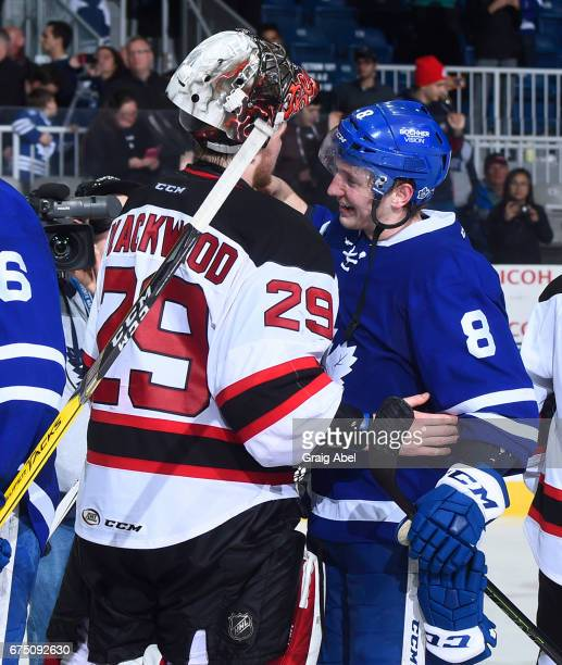 Travis Dermott of the Toronto Marlies shakes hands with Mackenzie Blackwood of the Albany Devils after game 4 action in the Division Semifinal of the...