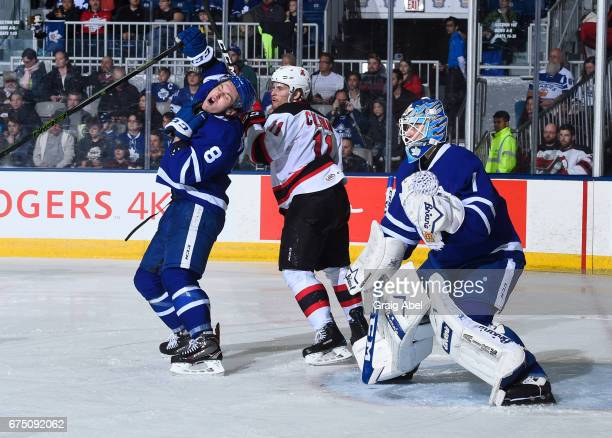 Travis Dermott of the Toronto Marlies takes a stick to the head by Blake Coleman of the Albany Devils in front of Marlie goalie Kasimir Kaskisuo...