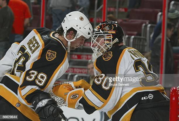 Travis Green and goaltender Tim Thomas of the Boston Bruins butt helmets in celebration following their 52 win over the Philadelphia Flyers on...