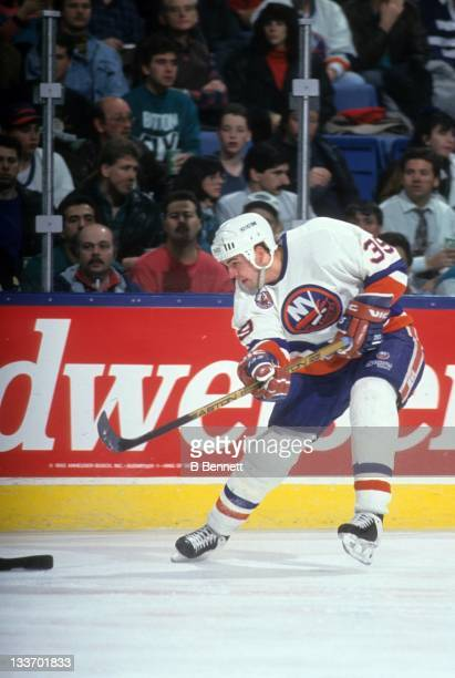 Travis Green of the New York Islanders shoots during an NHL game in January 1993 at the Nassau Coliseum in Uniondale New York