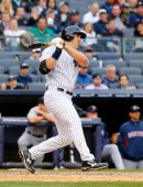 Travis Hafner of the New York Yankees follows through on an eighth inning base hit against the Boston Red Sox during Opening Day at Yankee Stadium on...
