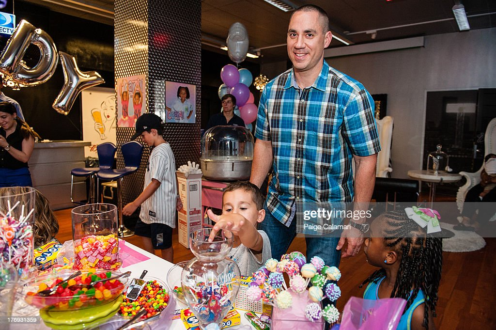 Travis Hafner of the New York Yankees helps his son to candy following the preview of the CCandy line during the CCandy Fashion Show at the MLB Fan...
