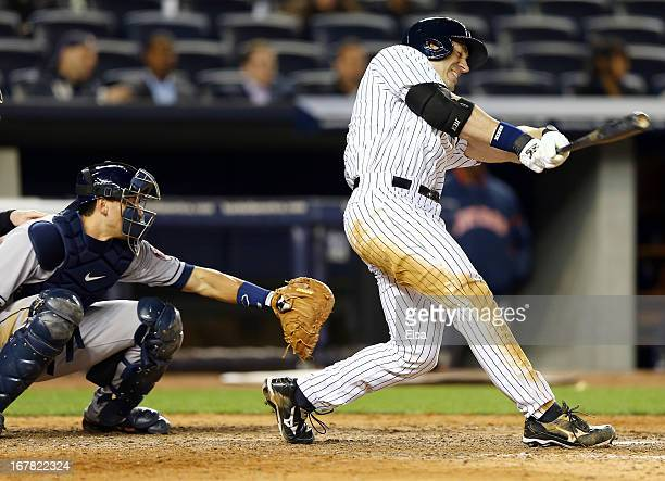 Travis Hafner of the New York Yankees hits his third RBI of the night as Jason Castro of the Houston Astros catches on April 30 2013 at Yankee...