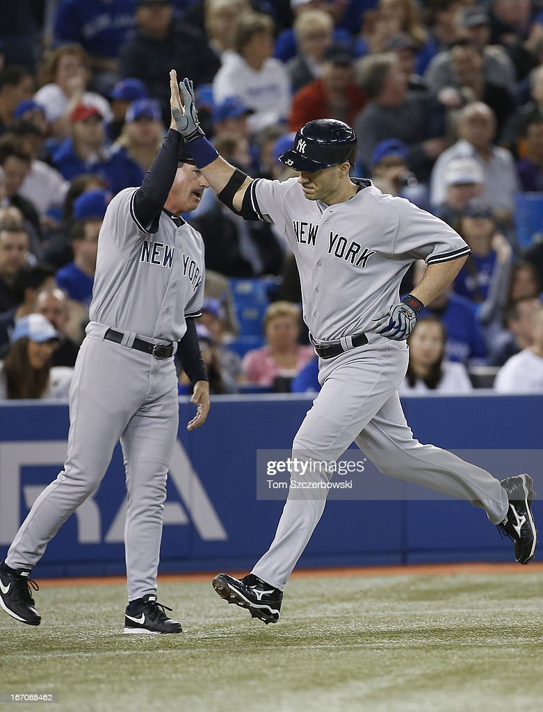 <a gi-track='captionPersonalityLinkClicked' href=/galleries/search?phrase=Travis+Hafner&family=editorial&specificpeople=220556 ng-click='$event.stopPropagation()'>Travis Hafner</a> #33 of the New York Yankees is congratulated by third base coach Rob Thomson #59 after hitting a solo home run in the third inning during MLB game action against the Toronto Blue Jays on April 19, 2013 at Rogers Centre in Toronto, Ontario, Canada.