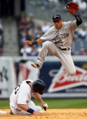 Travis Hafner of the New York Yankees is out at second as Jose Iglesias of the Boston Red Sox leaps over him while turning the double play during...