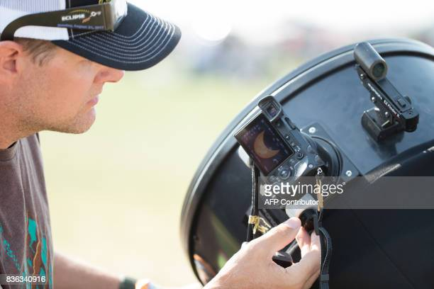 Travis Hammond records a stage of the total solar eclipse using a large personal telescope with a digital camera attached on August 21 2017 in Madras...
