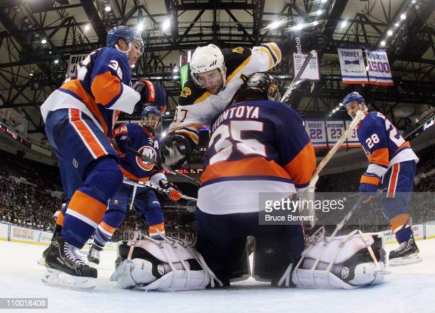 Travis Hamonic and Al Montoya of the New York Islanders defend the net against Patrice Bergeron of the Boston Bruins at the Nassau Coliseum on March...