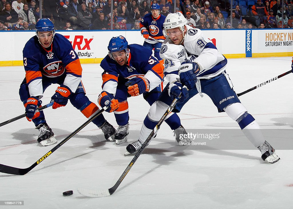 Travis Hamonic #3 and <a gi-track='captionPersonalityLinkClicked' href=/galleries/search?phrase=Frans+Nielsen&family=editorial&specificpeople=634894 ng-click='$event.stopPropagation()'>Frans Nielsen</a> #51 of the New York Islanders defend against <a gi-track='captionPersonalityLinkClicked' href=/galleries/search?phrase=Steven+Stamkos&family=editorial&specificpeople=4047623 ng-click='$event.stopPropagation()'>Steven Stamkos</a> #91 of the Tampa Bay Lightning at the Nassau Veterans Memorial Coliseum on January 21, 2013 in Uniondale, New York. The Islanders defeated the Lightning 4-3.