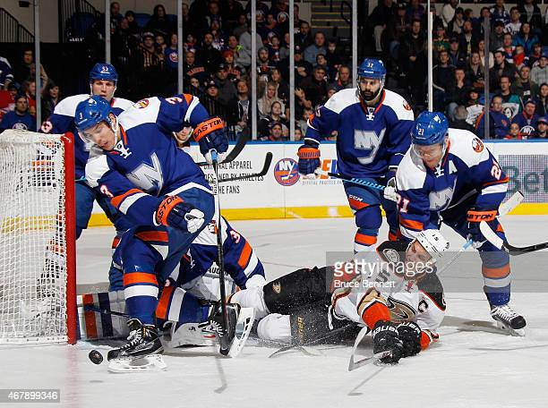 Travis Hamonic and Kyle Okposo of the New York Islanders defend against Ryan Getzlaf of the Anaheim Ducks during the first period at the Nassau...