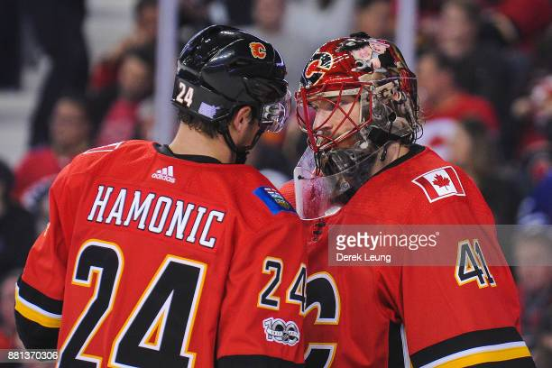 Travis Hamonic and Mike Smith of the Calgary Flames confer during a break in play against the Toronto Maple Leafs during an NHL game at Scotiabank...