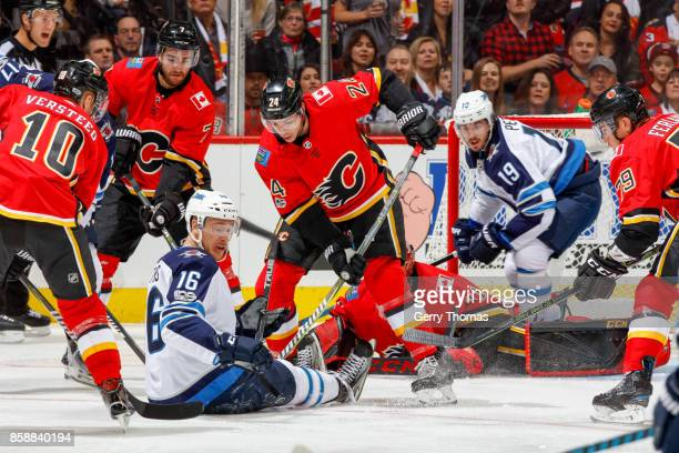 Travis Hamonic of the Calgary Flames and Shawn Matthias of the Winnipeg Jets fight for the puck during an NHL game against the Winnipeg Jets at the...