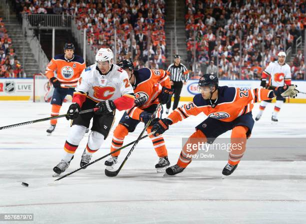 Travis Hamonic of the Calgary Flames battles for the puck against Kailer Yamamoto and Darnell Nurse on October 4 2017 at Rogers Place in Edmonton...