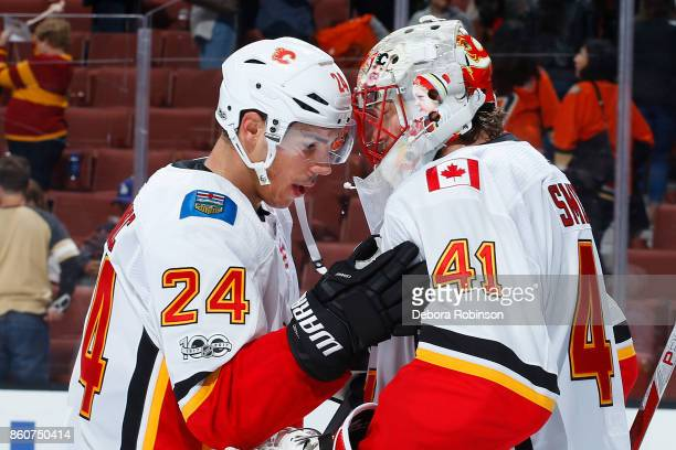 Travis Hamonic of the Calgary Flames congratulates Mike Smith after a shutout win against the Anaheim Ducks on October 9 2017 at Honda Center in...