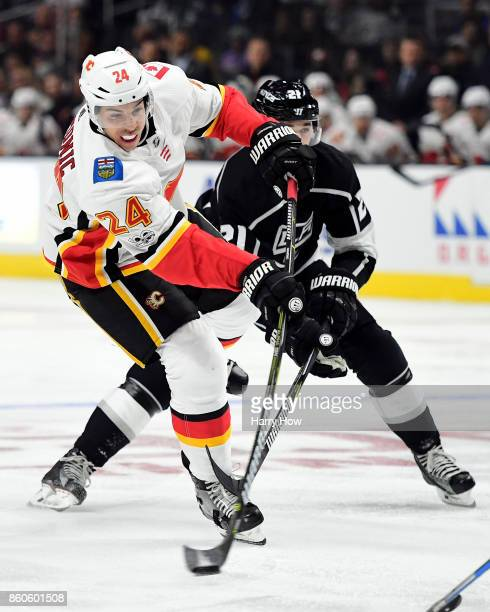Travis Hamonic of the Calgary Flames takes a shot as he is checked by Nick Shore of the Los Angeles Kings at Staples Center on October 11 2017 in Los...