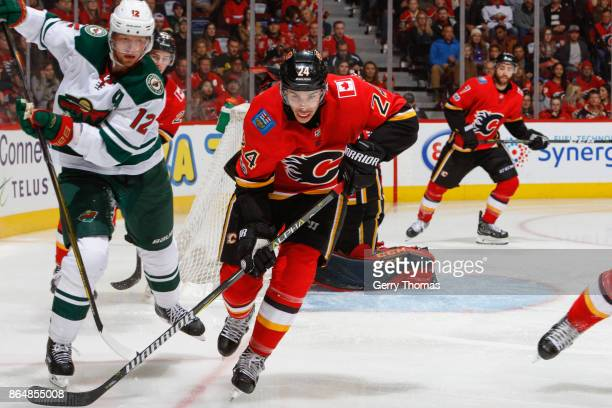 Travis Hamonic of the Calgary Flames tries to steal a pass from Eric Staal of the Minnesota Wild in an NHL game against the Minnesota Wild at the...