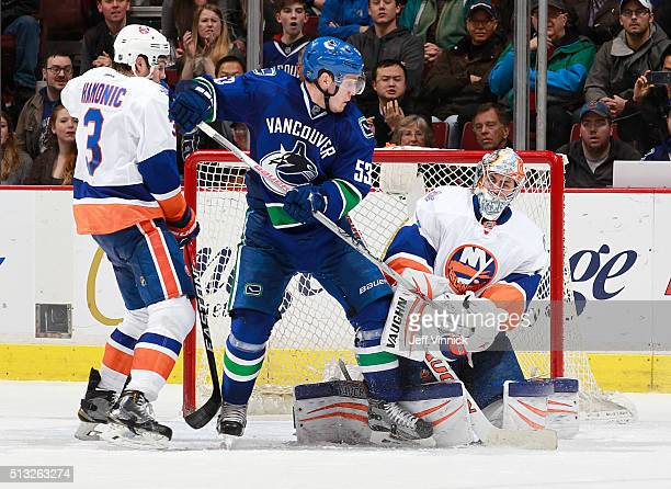 Travis Hamonic of the New York Islanders and Bo Horvat of the Vancouver Canucks watch Thomas Greiss of the Islanders make a save during their NHL...