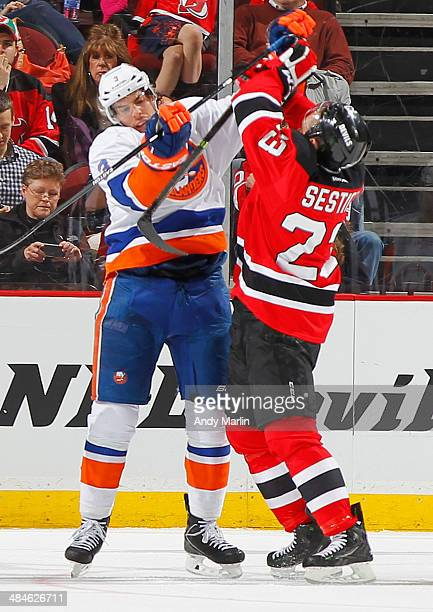 Travis Hamonic of the New York Islanders and Tim Sestito of the New Jersey Devils come together during the game at the Prudential Center on April 11...