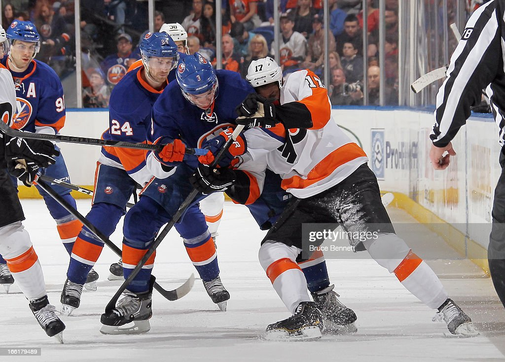 Travis Hamonic #3 of the New York Islanders and Wayne Simmonds #17 of the Philadelphia Flyers get tied up at the Nassau Veterans Memorial Coliseum on April 9, 2013 in Uniondale, New York.