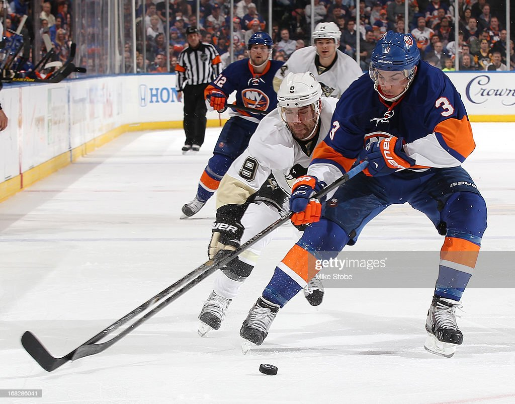 <a gi-track='captionPersonalityLinkClicked' href=/galleries/search?phrase=Travis+Hamonic&family=editorial&specificpeople=4605791 ng-click='$event.stopPropagation()'>Travis Hamonic</a> #3 of the New York Islanders battles for the puck against <a gi-track='captionPersonalityLinkClicked' href=/galleries/search?phrase=Pascal+Dupuis&family=editorial&specificpeople=208971 ng-click='$event.stopPropagation()'>Pascal Dupuis</a> #9 of the Pittsburgh Penguins in Game Four of the Eastern Conference Quarterfinals during the 2013 NHL Stanley Cup Playoffs at Nassau Veterans Memorial Coliseum on May 7, 2013 in Uniondale, New York. The Islanders defeated the Penguins 6-4.
