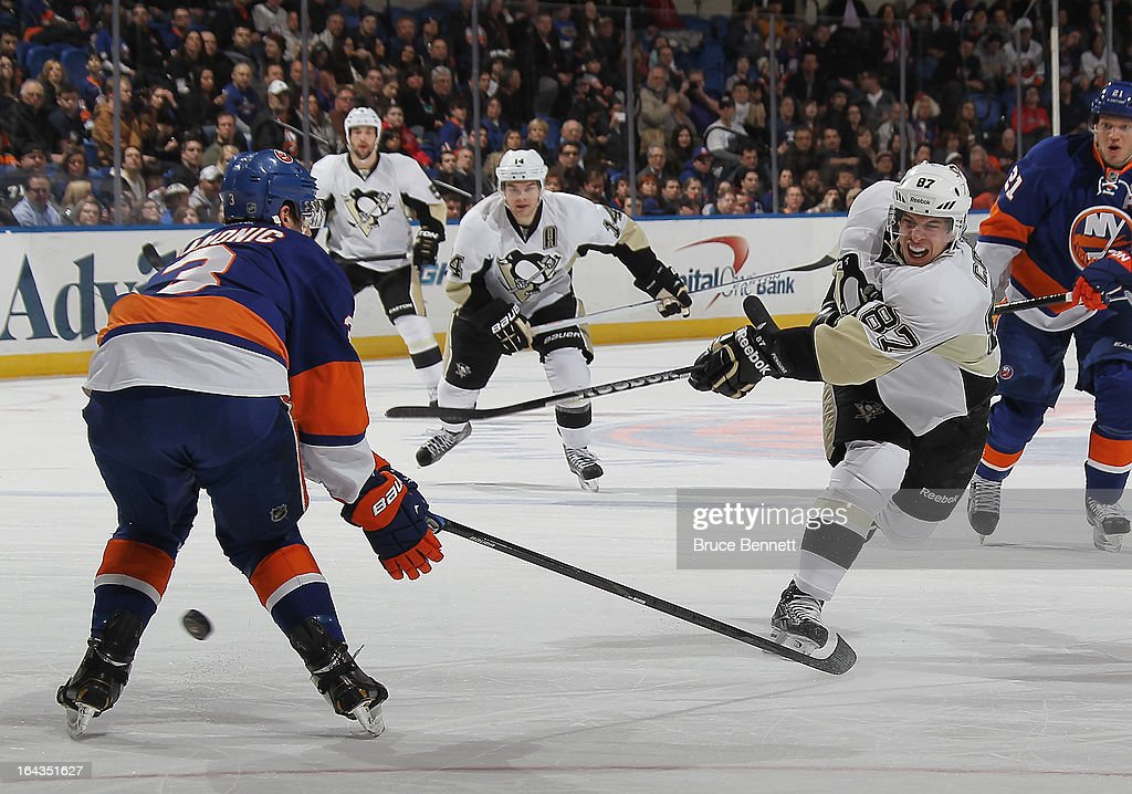 Travis Hamonic #3 of the New York Islanders blocks a shot by Sidney Crosby #87 of the Pittsburgh Penguins at Nassau Veterans Memorial Coliseum on March 22, 2013 in Uniondale, New York. The Penguins defeated the Islanders 4-2.