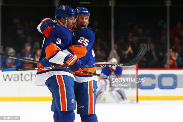Travis Hamonic of the New York Islanders celebrates his first period goal with teammate Jason Chimera against the Columbus Blue Jackets at the...