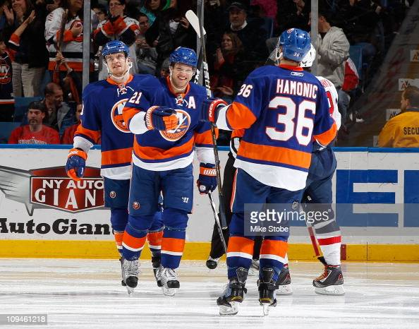 Travis Hamonic of the New York Islanders celebrates his second period goal with teammates Kyle Okposo and Michael Grabner in a game against the...