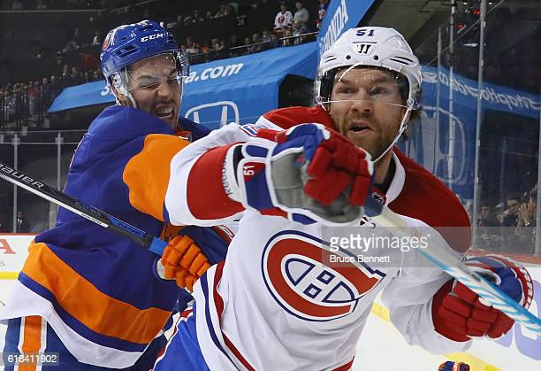 Travis Hamonic of the New York Islanders checks David Desharnais of the Montreal Canadiens during the first period at the Barclays Center on October...