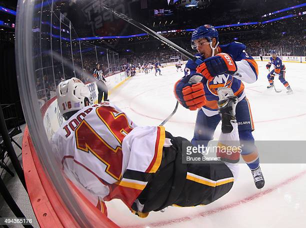 Travis Hamonic of the New York Islanders checks Josh Jooris of the Calgary Flames into the boards during the first period at the Barclays Center on...