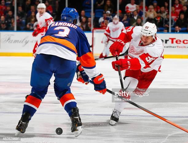 Travis Hamonic of the New York Islanders defends against Stephen Weiss of the Detroit Red Wings at Nassau Veterans Memorial Coliseum on November 29...