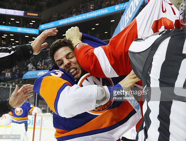Travis Hamonic of the New York Islanders fights with Steve Ott of the Detroit Red Wings during the first period at the Barclays Center on December 4...