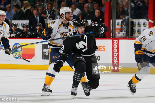 Travis Hamonic of the New York Islanders gets tripped up against James Neal of the Nashville Predators at Barclays Center on March 27 2017 in the...
