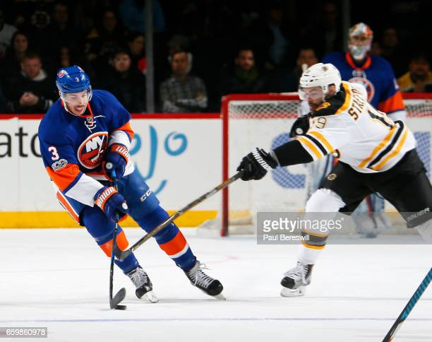 Travis Hamonic of the New York Islanders handles the puck against Drew Stafford of the Boston Bruins during an NHL hockey game at the Barclays Center...