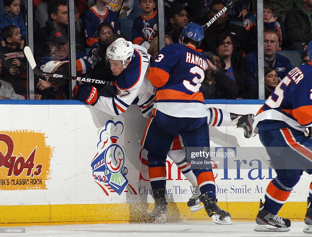 Travis Hamonic #3 of the New York Islanders hits Anton Lander #57 of the Edmonton Oilers into the boards at the Nassau Veterans Memorial Coliseum on December 31, 2011 in Uniondale, New York.