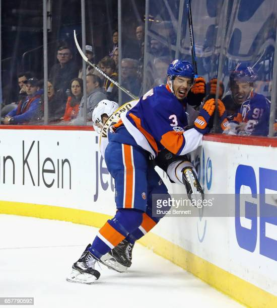 Travis Hamonic of the New York Islanders hits Frank Vatrano of the Boston Bruins into the boards during the second period at the Barclays Center on...