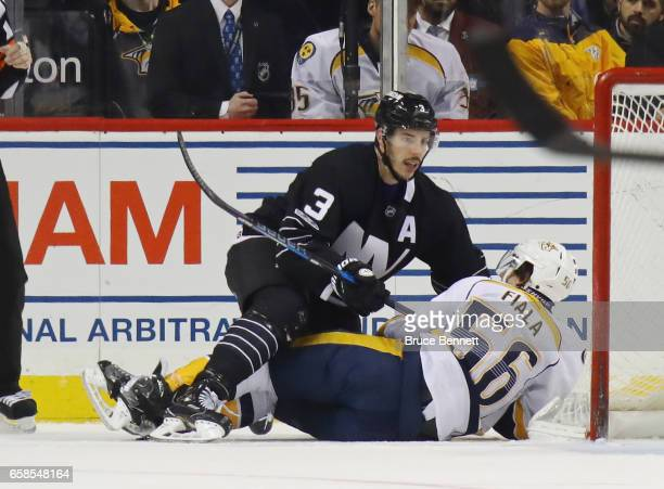 Travis Hamonic of the New York Islanders hits Kevin Fiala of the Nashville Predators during the second period at the Barclays Center on March 27 2017...