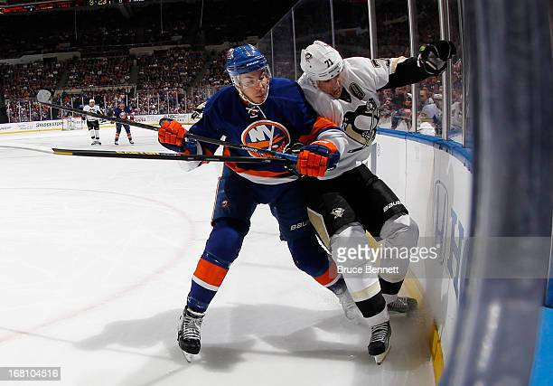 Travis Hamonic of the New York Islanders hits Sidney Crosby of the Pittsburgh Penguins into the boards in Game Three of the Eastern Conference...