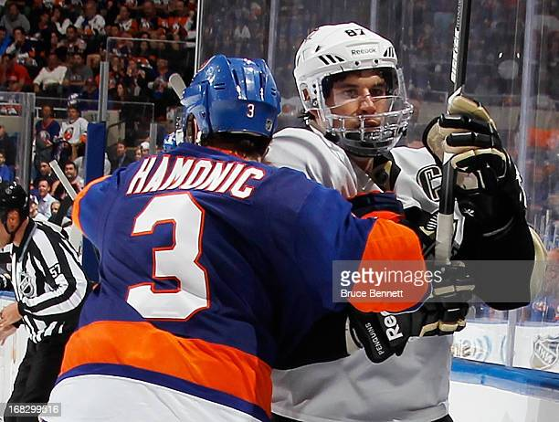 Travis Hamonic of the New York Islanders hits Sidney Crosby of the Pittsburgh Penguins into the boards in Game Four of the Eastern Conference...