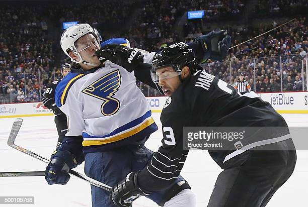Travis Hamonic of the New York Islanders hits Vladimir Tarasenko of the St Louis Blues at the Barclays Center on December 4 2015 in Brooklyn borough...