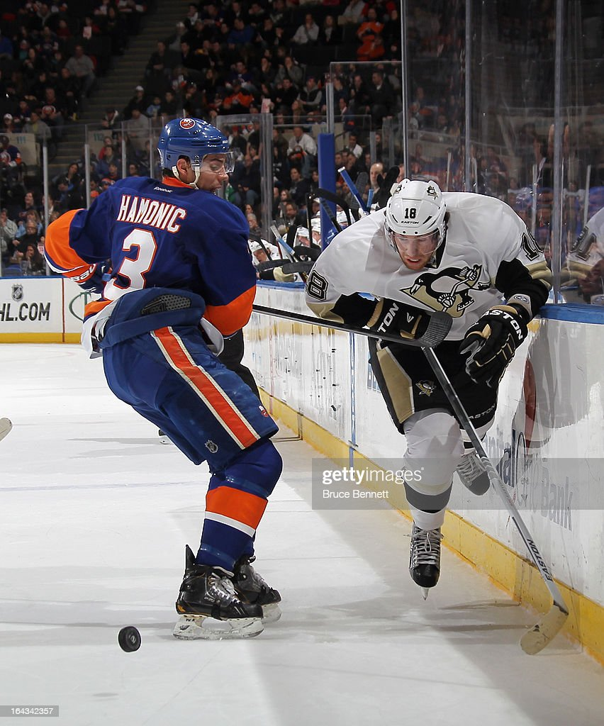 Travis Hamonic #3 of the New York Islanders holds up James Neal #18 of the Pittsburgh Penguins at Nassau Veterans Memorial Coliseum on March 22, 2013 in Uniondale, New York.