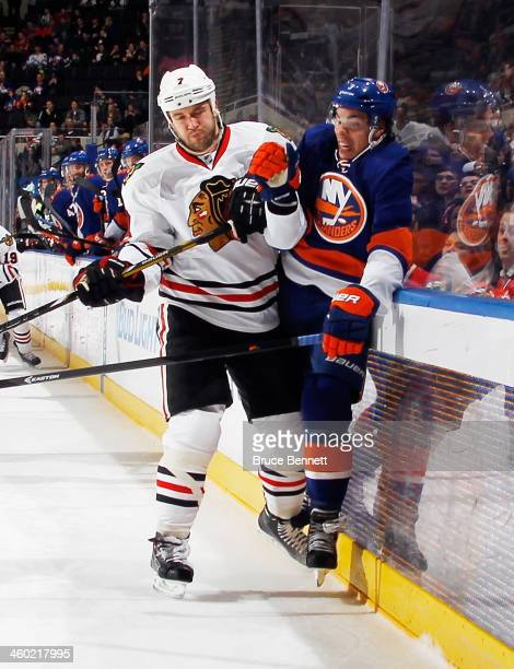 Travis Hamonic of the New York Islanders is hit into the boards by Brent Seabrook of the Chicago Blackhawks at the Nassau Veterans Memorial Coliseum...