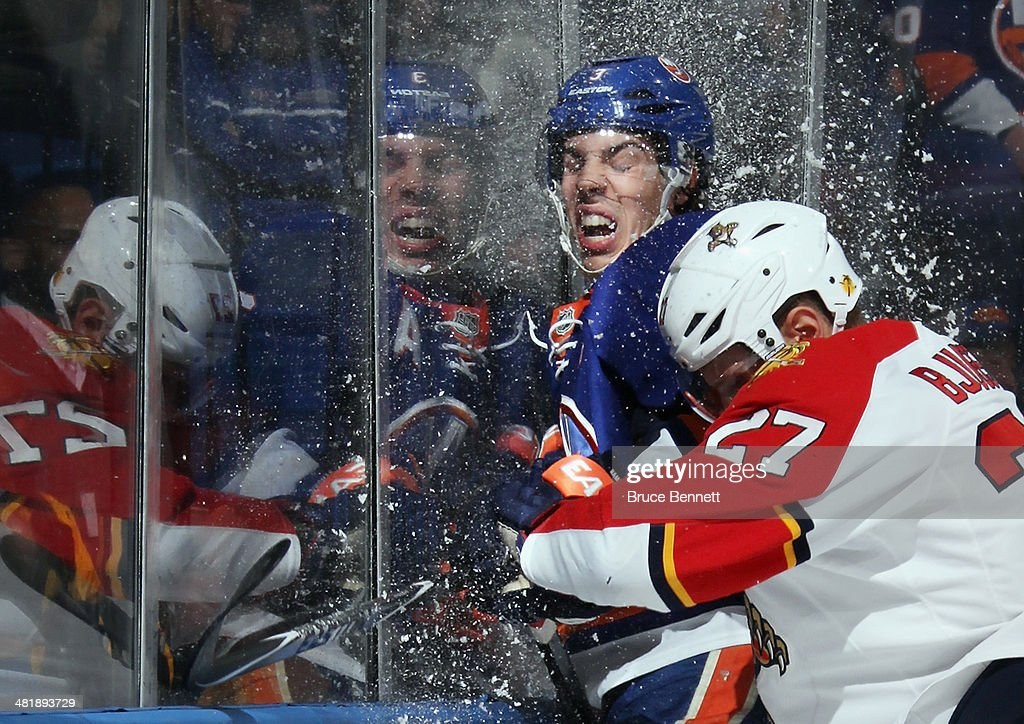 <a gi-track='captionPersonalityLinkClicked' href=/galleries/search?phrase=Travis+Hamonic&family=editorial&specificpeople=4605791 ng-click='$event.stopPropagation()'>Travis Hamonic</a> #3 of the New York Islanders is hit into the glass by <a gi-track='captionPersonalityLinkClicked' href=/galleries/search?phrase=Nick+Bjugstad&family=editorial&specificpeople=7029343 ng-click='$event.stopPropagation()'>Nick Bjugstad</a> #27 of the Florida Panthers during the first period at the Nassau Veterans Memorial Coliseum on April 1, 2014 in Uniondale, New York.