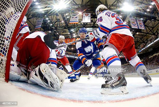 Travis Hamonic of the New York Islanders is stopped by Henrik Lundqvist of the New York Rangers at Nassau Veterans Memorial Coliseum on January 27...