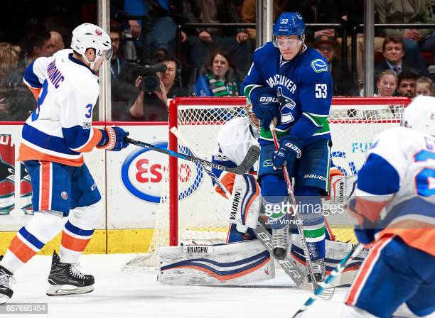 Travis Hamonic of the New York Islanders looks on as Bo Horvat of the Vancouver Canucks screens Thomas Greiss of the New York Islanders during their...