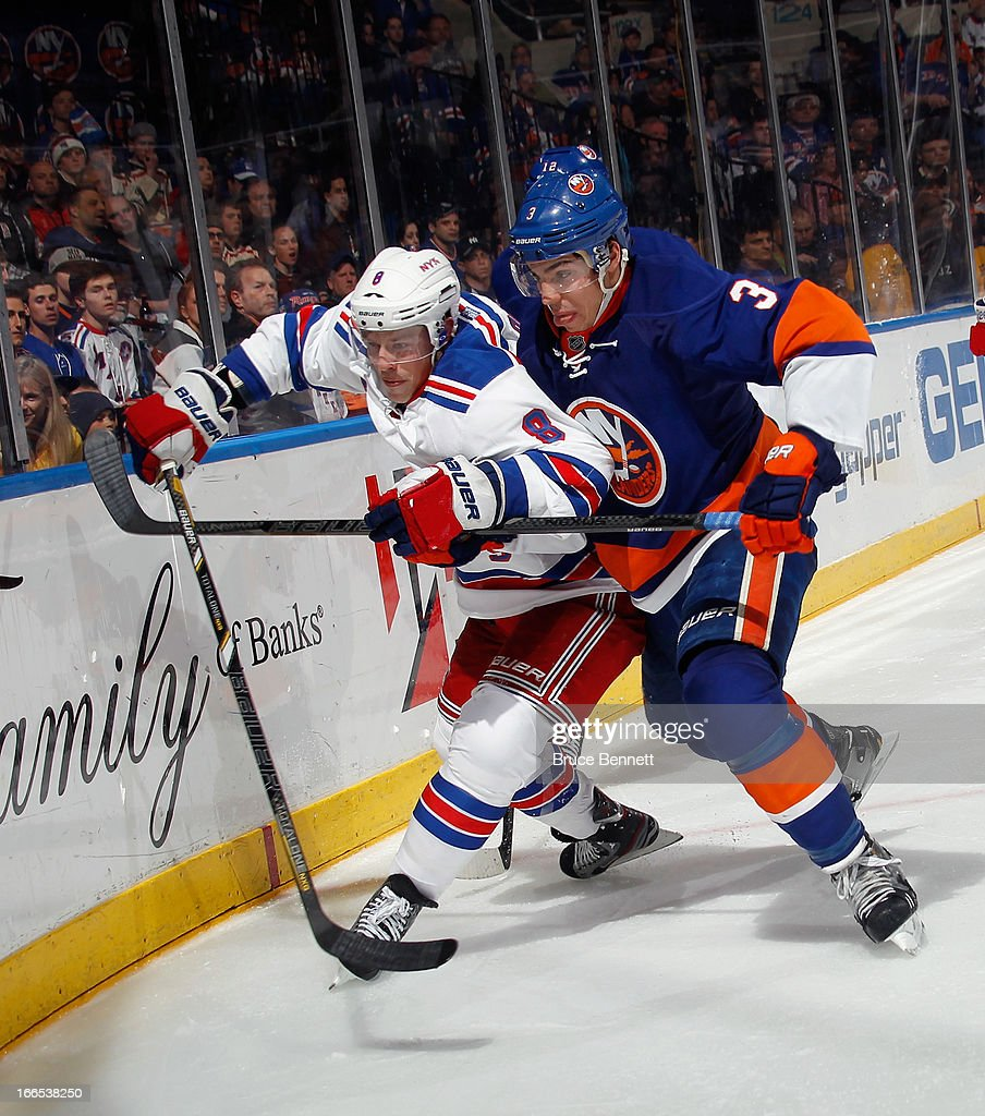 <a gi-track='captionPersonalityLinkClicked' href=/galleries/search?phrase=Travis+Hamonic&family=editorial&specificpeople=4605791 ng-click='$event.stopPropagation()'>Travis Hamonic</a> #3 of the New York Islanders runs <a gi-track='captionPersonalityLinkClicked' href=/galleries/search?phrase=Darroll+Powe&family=editorial&specificpeople=4527845 ng-click='$event.stopPropagation()'>Darroll Powe</a> #8 of the New York Rangers into the boards at the Nassau Veterans Memorial Coliseum on April 13, 2013 in Uniondale, New York. The Rangers defeated the Islanders inovertime 1-0.