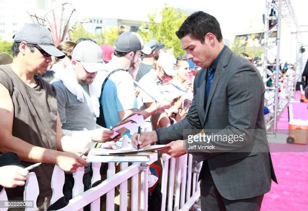 Travis Hamonic of the New York Islanders signs an autograph as he arrives on the magenta carpet for the 2017 NHL Awards at TMobile Arena on June 21...