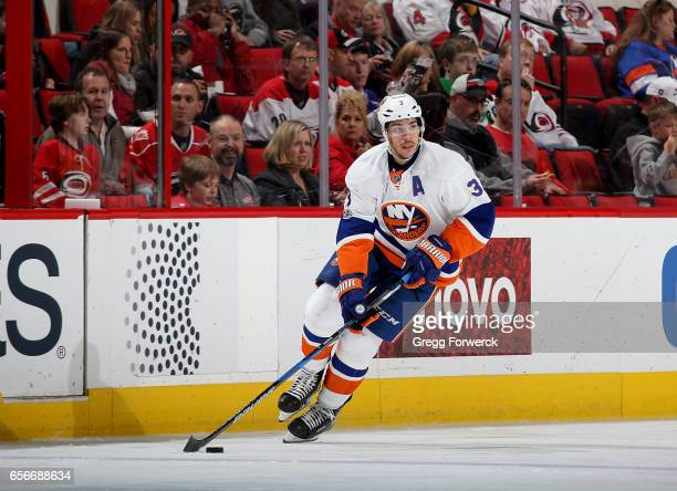 Travis Hamonic of the New York Islanders skates with the puck during an NHL game against the Carolina Hurricanes on March 14 2017 at PNC Arena in...